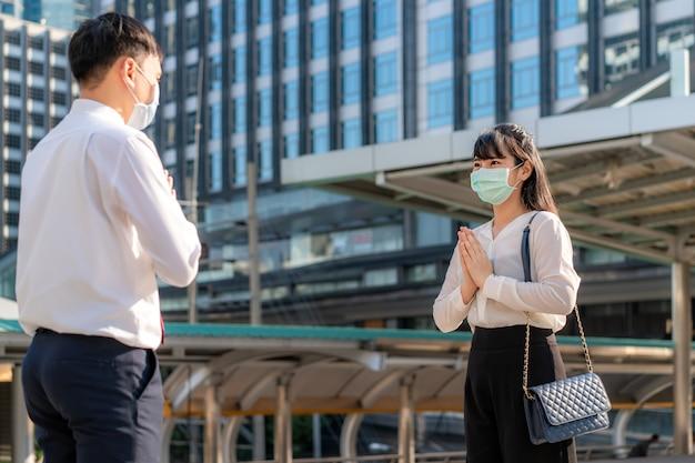 «уважай, это новое романтическое приветствие во избежание распространения коронавируса». два азиатских молодых бизнесмена и друзья встречаются в шрифте офисного здания. Premium Фотографии