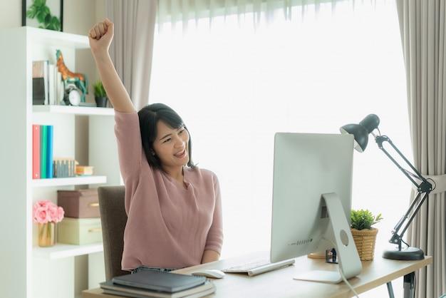 Красивая азиатская работа бизнес-леди от дома и празднует с компьютером, представлением успеха счастливым. Premium Фотографии