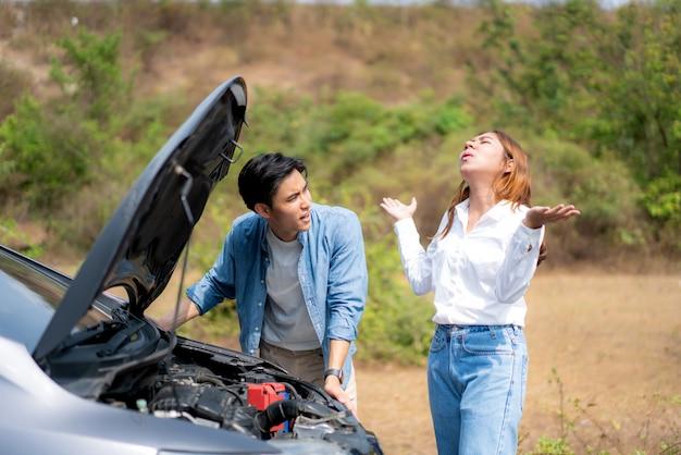 男と女が車を修理できないときにストレスを探している道と女の車のエンジンに問題の故障がある道路上の男と女とアジアの若いカップル。 Premium写真