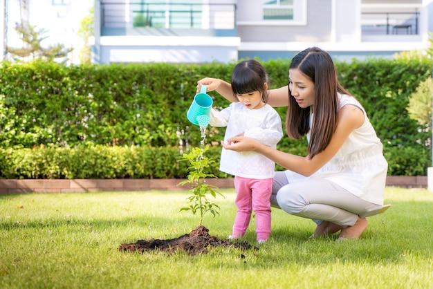 Азиатская семья мать и дочь дочь сажают дерево саженцев и полива на открытом воздухе в природе весной для снижения роста глобального потепления и заботиться о природе земли. Premium Фотографии