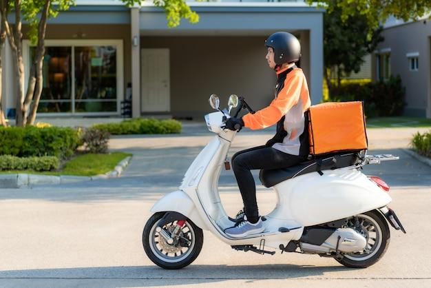テイクアウトやレストランから家庭への熱い食べ物の配達で町の通りに食べ物を届けるスクーターでアジア人男性宅配便、速達配達、ショッピングオンラインコンセプト。 Premium写真