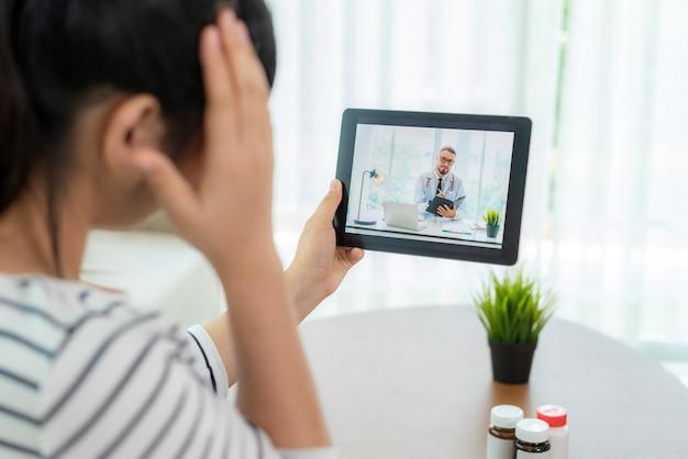 家にいる間、デジタルタブレットオンラインヘルスケアデジタルテクノロジーサービスの相談に彼女の頭痛で彼女の医者とビデオ通話を行う若い女性の背面図。 Premium写真