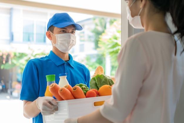 Азиатский доставщик, носящий маску и перчатку с бакалейной коробкой с едой, фруктами, овощами и напитками, дает женщине клиент перед домом во время домашней изоляции. Premium Фотографии