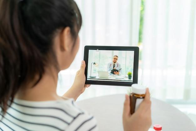 ビデオ会議を使用してアジアの年配の女性は、ビデオコールを介して病気や投薬について相談している医師とオンラインで相談します。遠隔医療、遠隔医療、オンライン病院。 Premium写真