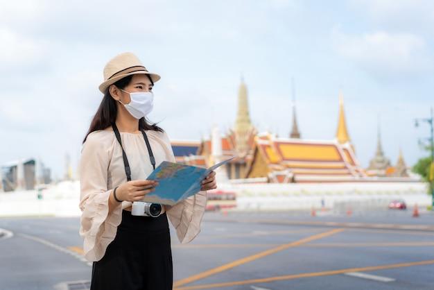 Туристы азиатской женщины счастливые для того чтобы путешествовать нося маска Premium Фотографии