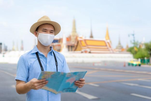 Туристы азиатского человека счастливые для того чтобы путешествовать нося маска Premium Фотографии