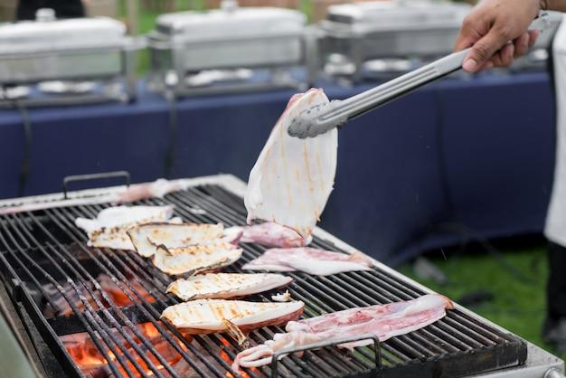 シェフはイカをアジアのスパイスで焼き上げて調理しています Premium写真