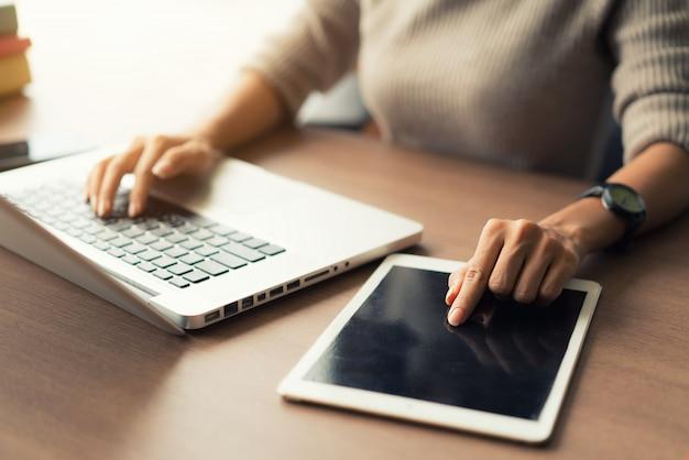 女性のオフィスでの作業中にラップトップとデジタルタブレットを使用して手をクローズアップ。 Premium写真