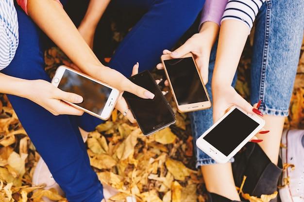 スマートな携帯電話を見ている友人のグループ手のクローズアップ Premium写真