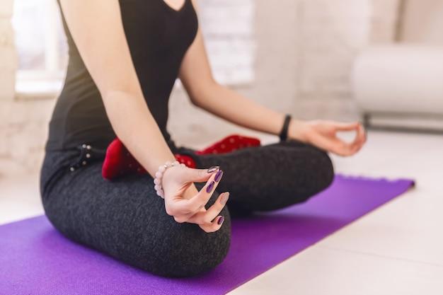 クローズアップマインドフル婦人、自宅で一人で瞑想、自由穏やかな穏やかな女の子ロータスポーズでヨガ Premium写真