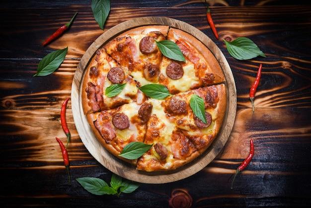 木製トレイと唐辛子バジルの葉の上のピザ Premium写真