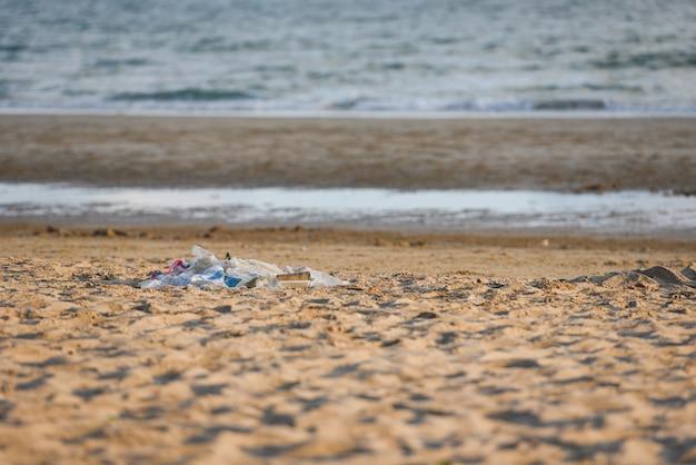 バッグペットボトルや島の他のゴミビーチ砂浜汚れた海と海のゴミ Premium写真