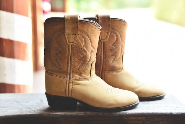カウボーイブーツアメリカの野生の西のレトロなカウボーイロデオ伝統的な革ローパースタイルの田舎で木製のビンテージスタイルの西部 Premium写真