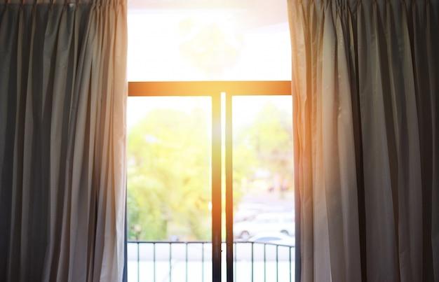 午前中に寝室の窓 - 部屋の中で太陽の光が窓の外にバルコニーと自然の木のカーテンを開く Premium写真