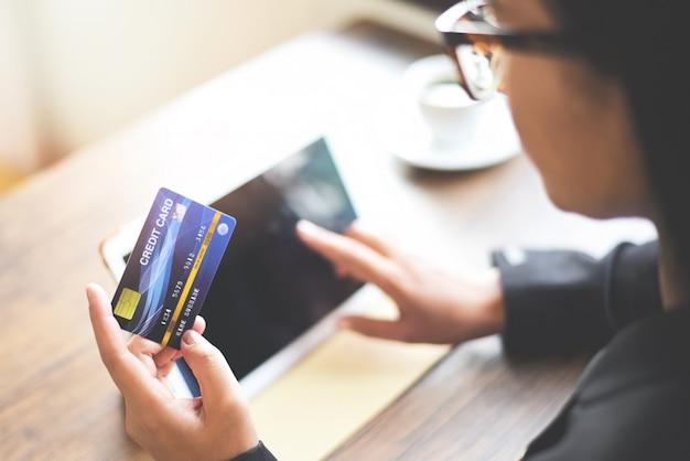 女性両手クレジットカードを使用してタブレットを使用してオンラインショッピング技術お金財布オンライン支払い Premium写真
