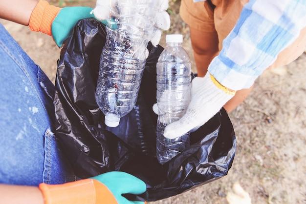 若い女性ボランティアのグループは、自然を清潔に保ち、公園からゴミペットボトルを拾うのを手伝っています。 Premium写真
