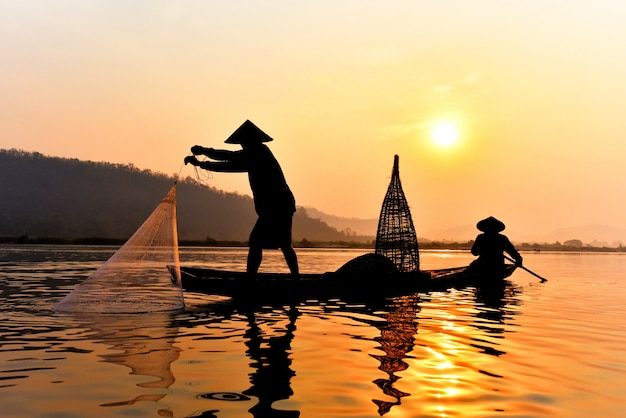 メコン川のネット日没または日の出を鋳造木製ボートに使用してアジア漁師ネット Premium写真
