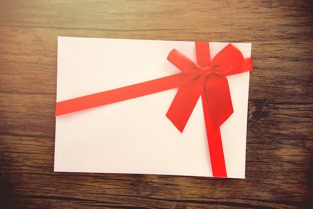 Подарочная карта на деревянном фоне розово-белый подарочная карта, украшенная красной ленточкой, к рождеству, новому году или дню святого валентина Premium Фотографии