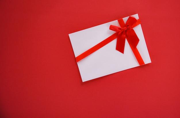 Подарочная карта на красном фоне с красной лентой лук подарочный сертификат на красном фоне вид сверху копией пространства Premium Фотографии
