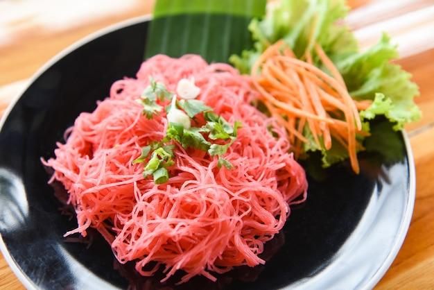 米春雨のピンクのフライパンと野菜の炒めた赤米炒め麺は、木製のテーブルのプレートで提供していますタイ風アジアンヌードル Premium写真