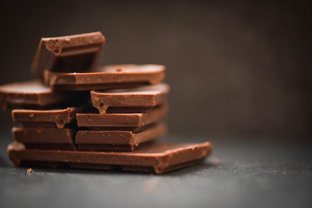 暗い背景に積み上げられたチョコレートバー Premium写真