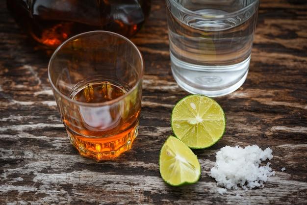 アルコール飲料とガラスのアルコールボトルと水でレモン塩木材背景ブランデー Premium写真