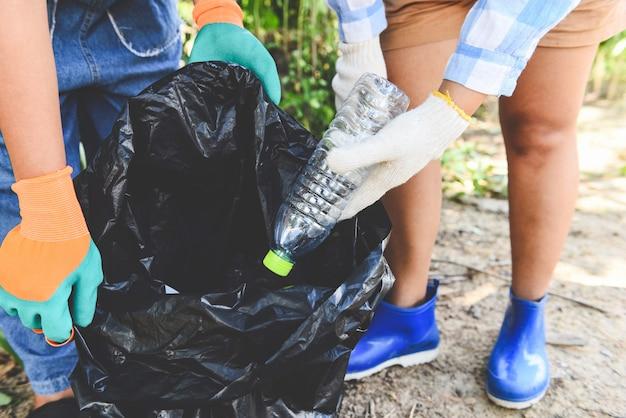 自然をきれいに保ち、ゴミを拾うのを助ける若い女性ボランティアのグループ Premium写真