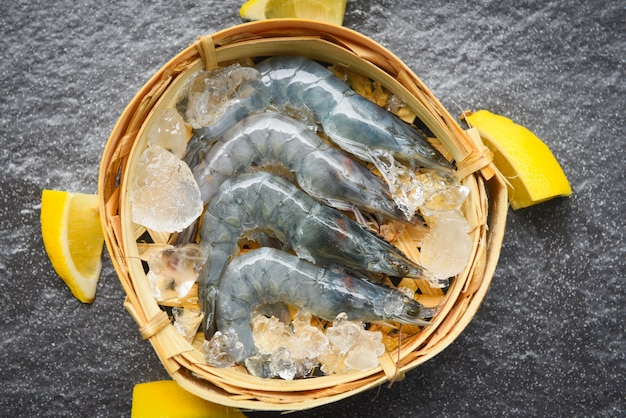 竹の蒸し器で生えび、アイススパイス、暗いプレートのレモン、レストランで新鮮なエビ Premium写真