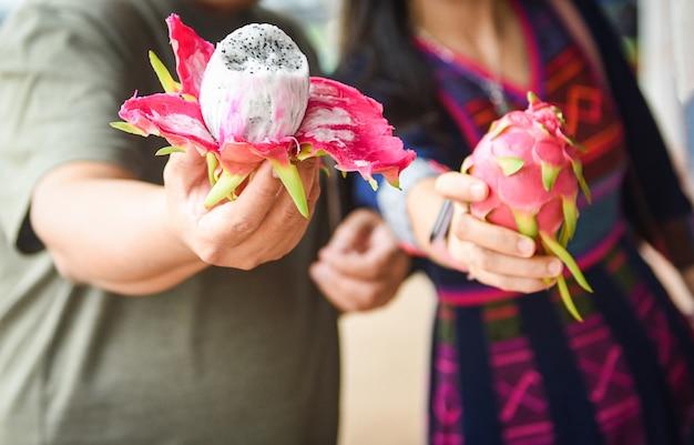 果物市場で手と女のドラゴンフルーツ新鮮なピタヤ Premium写真