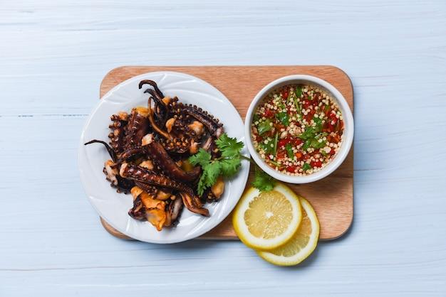 Салат из осьминога с лимонными травами и специями на белой тарелке Premium Фотографии