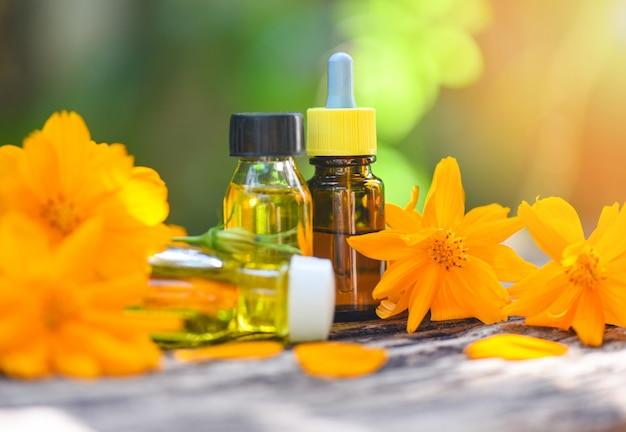 アロマテラピーハーブオイルボトルアロマネイチャーグリーンの花黄色顔と体の自然なエッセンシャルオイル木製のテーブルとオーガニックミニマリストライフスタイルの救済 Premium写真