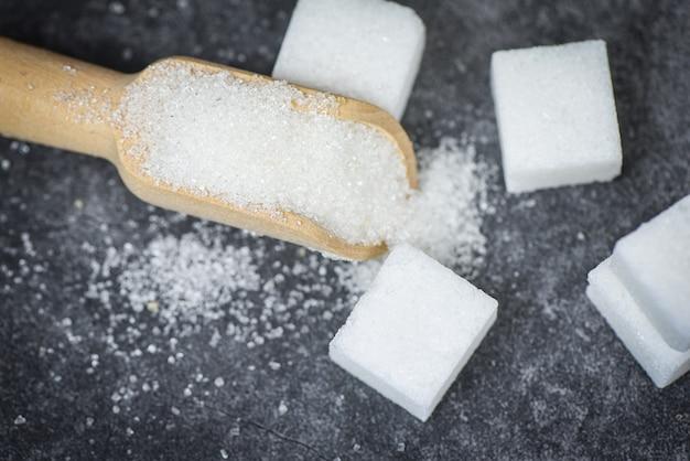 白い砂糖と暗い背景を持つ木製のスクープに砂糖キューブ Premium写真