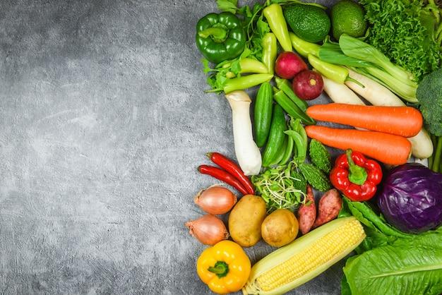 灰色の背景に新鮮な熟したフルーツ赤黄色紫と緑の野菜の混合選択の盛り合わせ Premium写真