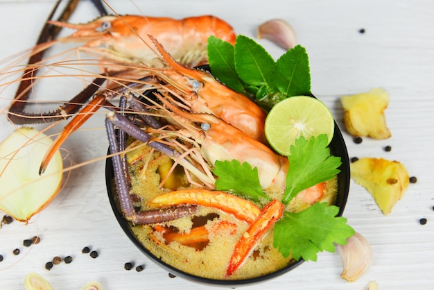 トムヤムクンタイ料理アジアの伝統的なエビのスパイシーなスープボウルシーフードエビスープディナーテーブルとスパイスの食材 Premium写真
