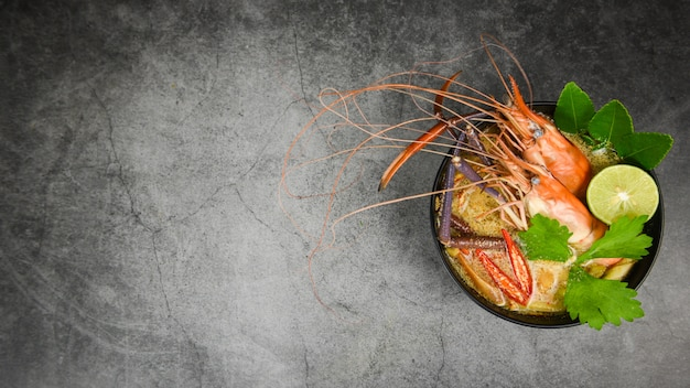 Тарелка супа с креветками и пряностями с добавлением ингредиентов на темноте приготовленные морепродукты с обеденным столом с супом из креветок тайская еда азиатская традиционная, том ям кунг Premium Фотографии