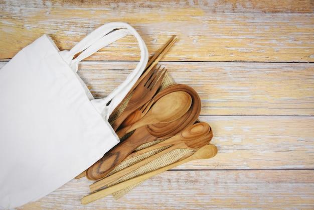 Натуральные кухонные инструменты изделия из дерева кухонная утварь с ложкой, вилка, палочки для еды, тарелка, разделочная доска, предмет и сумка из ткани. Premium Фотографии