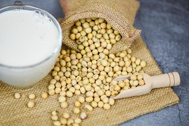 袋の大豆と白灰色のガラスの豆乳-牛乳の健康的な食事と天然の豆たんぱく質 Premium写真