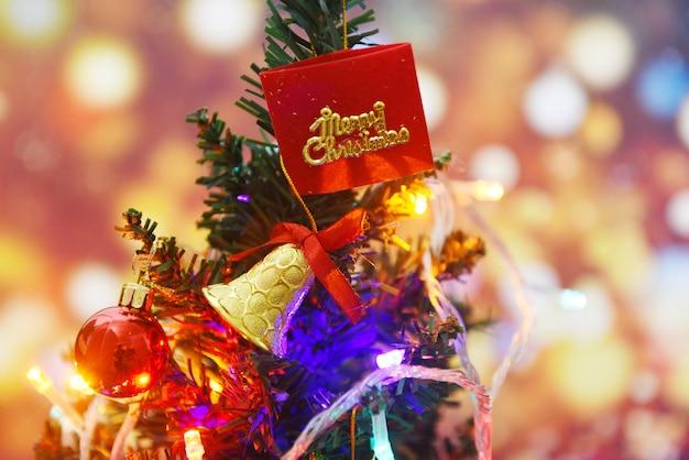 Красивое украшение елки на размытом разноцветном боке - ёлка с шаром, подарочная коробка, звезда и фонари, украшенная сосной, новогодние праздники, праздник празднования дома, интерьер Premium Фотографии