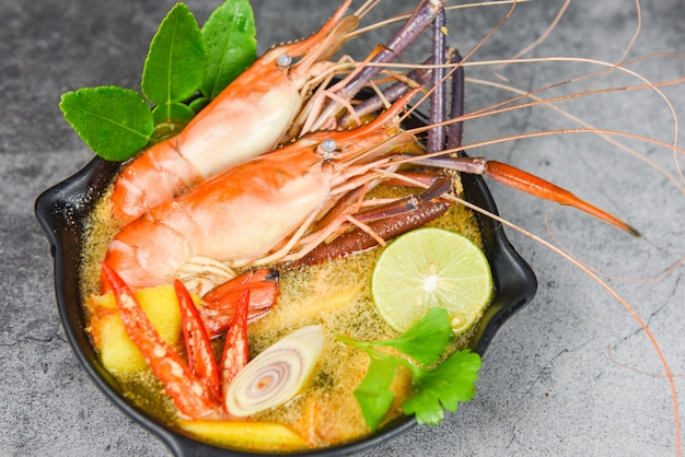 エビのスパイシーなスープボウルにスパイスの食材を使ったダーク-エビスープディナーテーブルタイ料理アジア料理、トムヤムクンと調理されたシーフード Premium写真