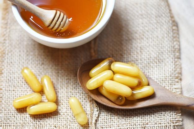 Капсулы маточного молочка в деревянной ложке на мешочке и мед в чашке - желтая капсула лекарство или дополнительная пища от природы для здоровья Premium Фотографии