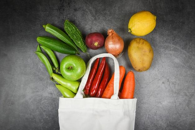 廃棄物ゼロのプラスチックコンセプトを採用-エココットン生地の袋に入れた新鮮な野菜や果物は、市場に出回っているプラスチックの買い物袋からテーブルトートキャンバス布バッグに Premium写真