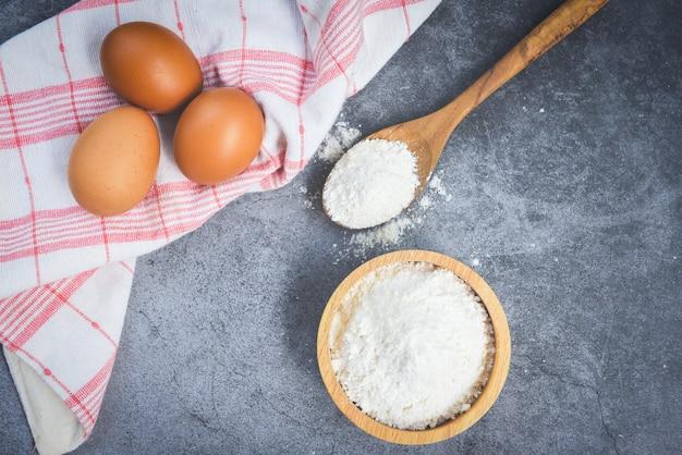 灰色の背景、トップビュー-木製のボウルにペストリー小麦粉 Premium写真