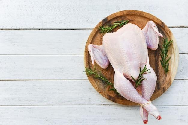 ローズマリー鶏肉/白い木製の背景に木の板に全体の新鮮な生鶏 Premium写真