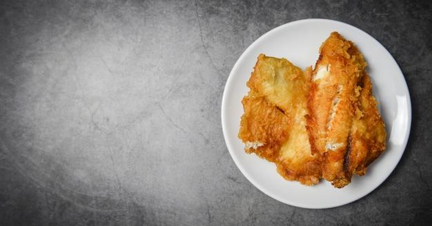 揚げ魚の切り身をステーキやサラダ料理、トップビューコピースペース-ティラピアの切り身魚クリスピー白いプレートで提供しています Premium写真