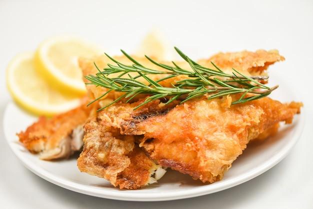 揚げ魚の切り身のステーキまたはサラダハーブスパイスローズマリーとレモン料理-ティラピアの切り身魚のサクサク白い皿 Premium写真
