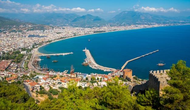 青い海と港都市背景-美しいクレオパトラビーチアラニヤトルコ風景旅行のランドマークの海岸フェリーボートと山のアラニヤビーチトップビュー Premium写真