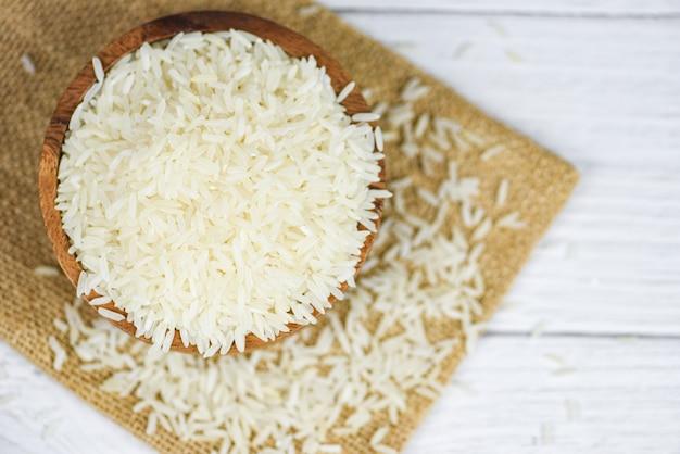 木製のボウルと袋に白いタイ米/生のジャスミン米穀物農産物のアジアの食品 Premium写真