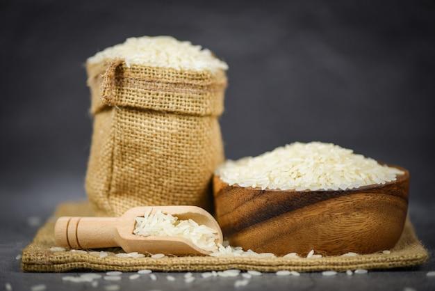 アジアの食糧のためのボウルと袋/生ジャスミン米粒農産物のタイ米白 Premium写真