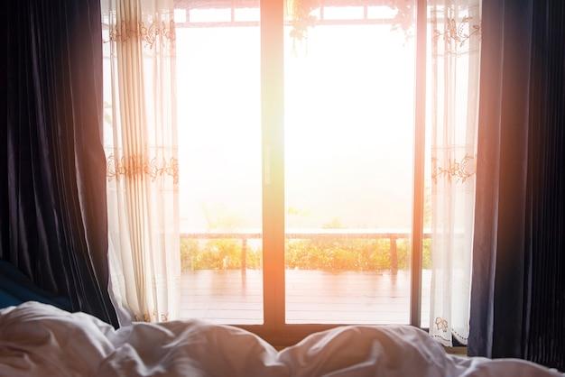 Окно с видом на природу зеленой горы в постели в спальне утром и солнечного света - оконное стекло с драпировкой Premium Фотографии