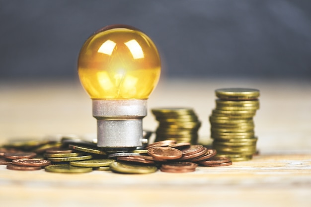 木製のテーブルに積み上げられたコインのランプからの光と電球。省エネのアイデア、節電、世界の概念 Premium写真